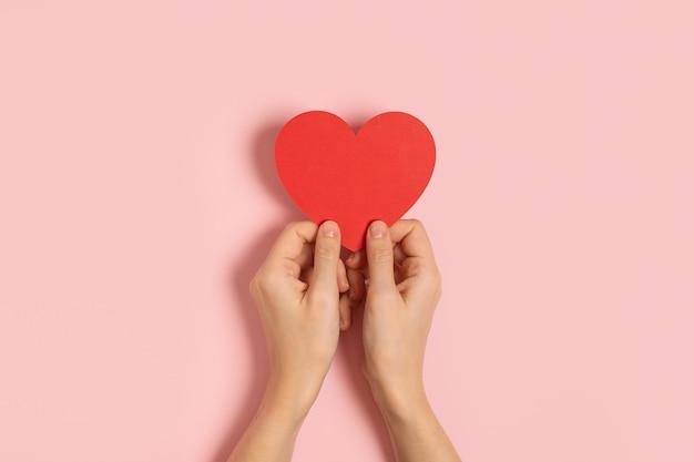 Draufsicht der frauenhände, die leeren papiergruß oder einladungskarte über rosa pastellhintergrund mit herzform halten