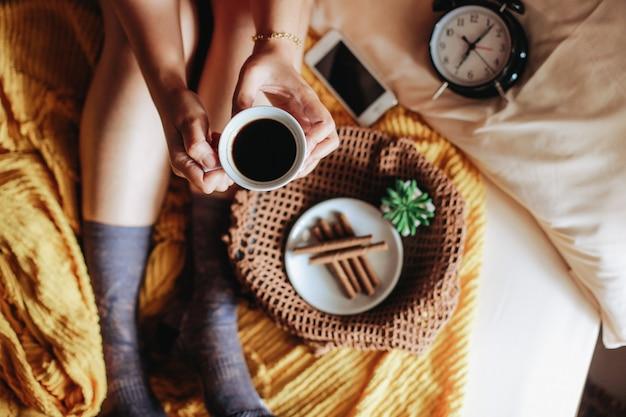 Draufsicht der frauenhand, die eine tasse kaffee mit leckerem snack für frühstück und uhr hält und 7 uhr und füße in warmer socke auf dem bett zeigt