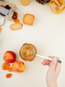 Draufsicht der frauenhand, die glasglas pfirsichmarmelade mit pfirsich-rosinen-cupcake auf weißer oberfläche hält