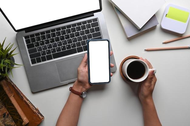 Draufsicht der frauenhand, die kaffeetasse hält und smartphone an ihrem schreibtisch mit laptop verwendet.