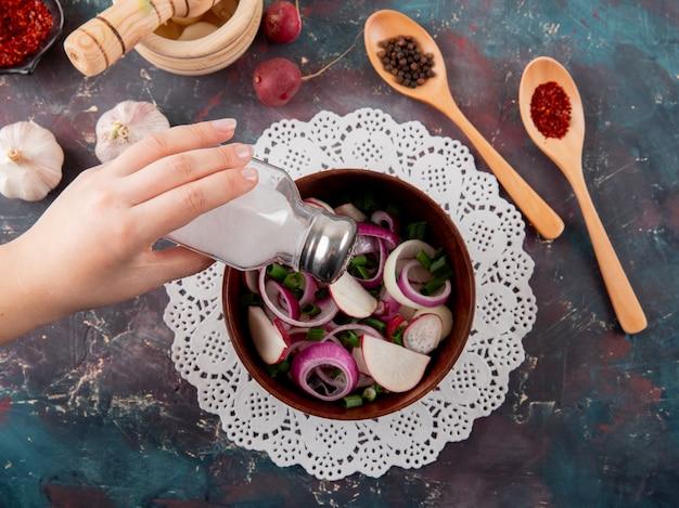 Draufsicht der frauenhand, die salz zu gemüsesalat mit gewürzen und knoblauch auf grünem und kastanienbraunem hintergrund hinzufügt