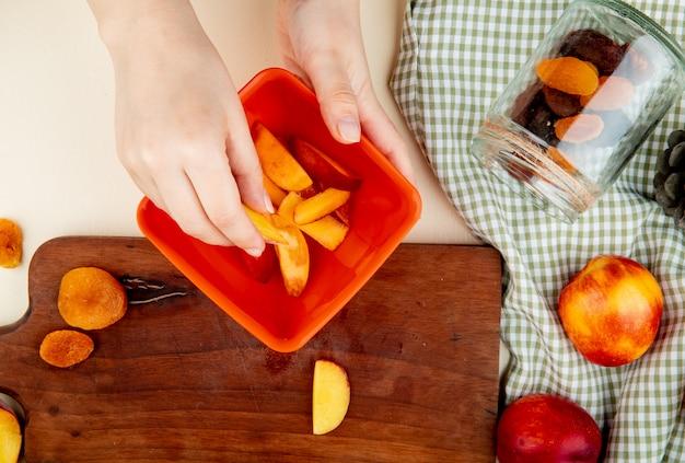 Draufsicht der frauenhand, die schüssel pfirsichscheiben mit getrockneten pflaumen auf schneidebrett und pfirsichen mit liegendem glas rosinen auf stoff und weißer oberfläche hält