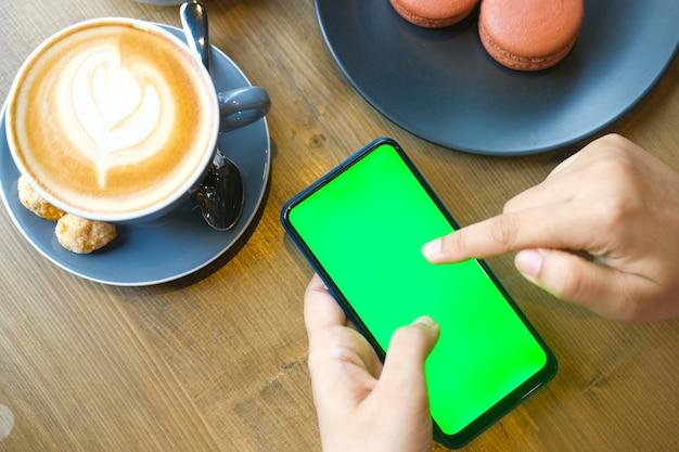 Draufsicht der frauenhand, die smartphone auf tisch hält