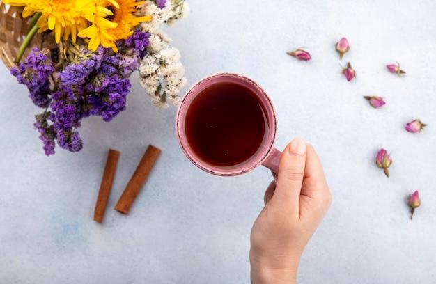 Draufsicht der frauenhand, die tasse tee mit zimt und blumen auf weißer oberfläche hält