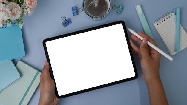 Draufsicht der frauenhand, die verspottetes digitales tablett und stift über pastellblaue oberfläche hält
