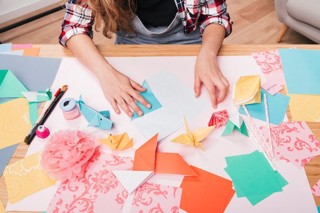 Draufsicht der frauenhand origamihandwerk auf tabelle vorbereitend