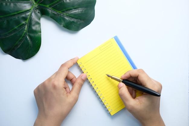 Draufsicht der frauenhandschrift auf notizblock auf weißem tisch.
