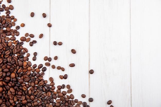 Draufsicht der frisch gerösteten kaffeebohnen lokalisiert auf einem weißen hölzernen hintergrund mit kopienraum