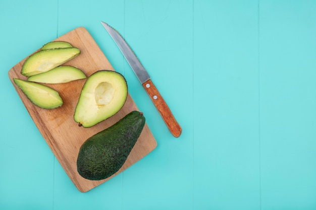 Draufsicht der frisch geschnittenen avocado mit messer auf holzküchenbrett auf blau