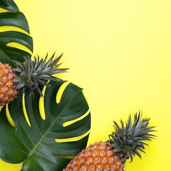 Draufsicht der frischen ananas mit tropischen palmen- und monstera-blättern auf gelbem tabellenhintergrund.
