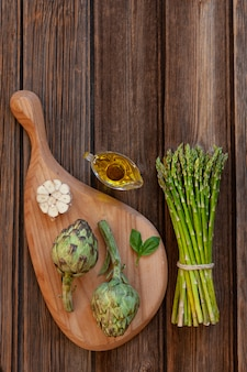 Draufsicht der frischen artischocke und des bündels grünem spargel mit knoblauch und olivenöl auf holztisch