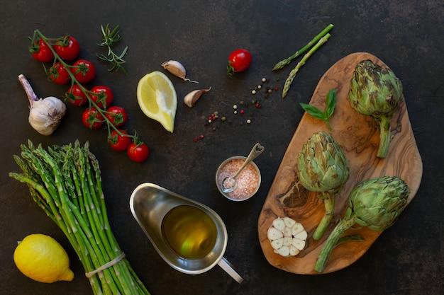 Draufsicht der frischen artischocke und des bündels grünen spargels mit olivenöl, tomaten, zitrone und knoblauch auf tabelle