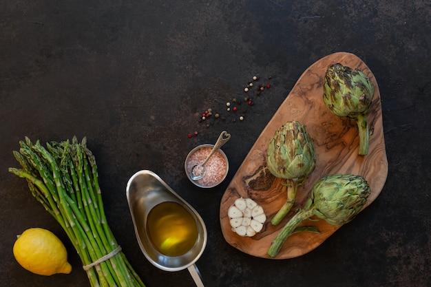 Draufsicht der frischen artischocke und des bündels grünen spargels mit olivenöl, zitrone und knoblauch auf tabelle