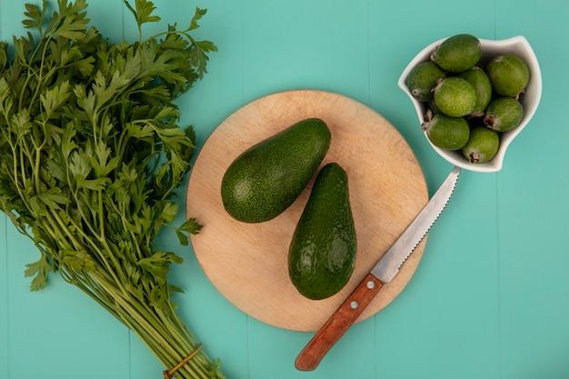 Draufsicht der frischen avocados auf einem hölzernen küchenbrett mit messer mit feijoas auf einer schüssel auf einer blauen wand