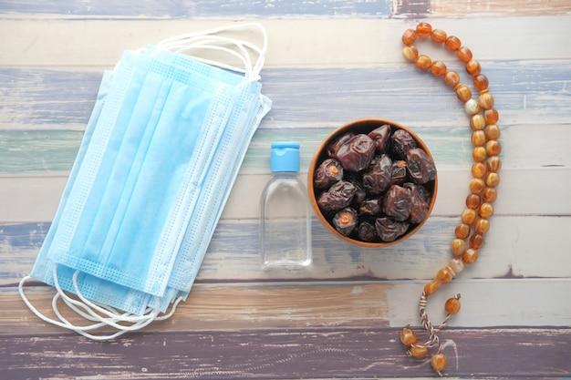 Draufsicht der frischen dattelfrucht der händedesinfektionsgesichtsmaske auf tisch