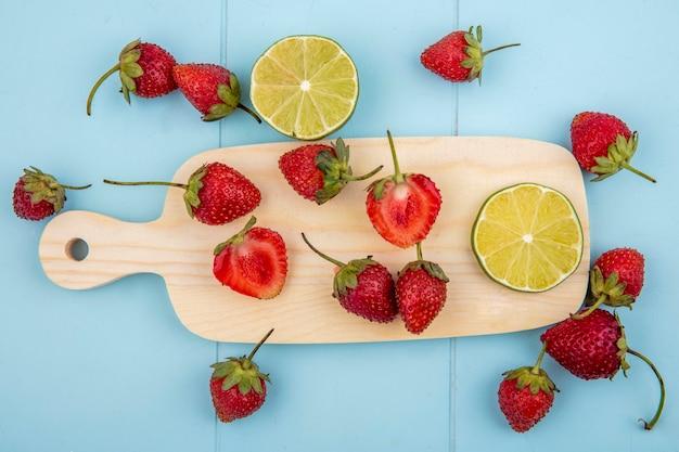 Draufsicht der frischen erdbeere auf einem hölzernen küchenbrett mit zitronenscheiben auf einem blauen hintergrund