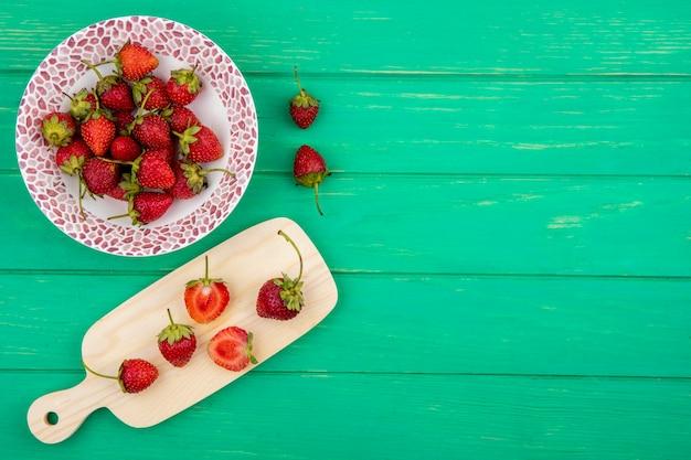 Draufsicht der frischen erdbeeren auf einer schüssel mit erdbeerscheiben auf einem hölzernen küchenbrett mit kopienraum