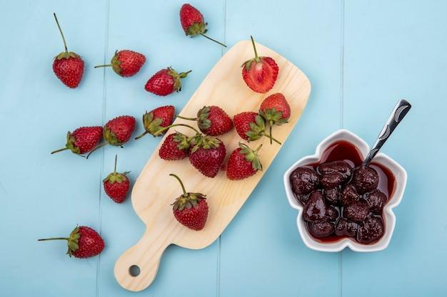 Draufsicht der frischen erdbeeren lokalisiert auf einem hölzernen küchenbrett mit einer erdbeermarmelade auf einer schüssel auf einem blauen hintergrund