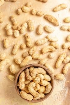 Draufsicht der frischen erdnüsse auf hölzernem schreibtisch
