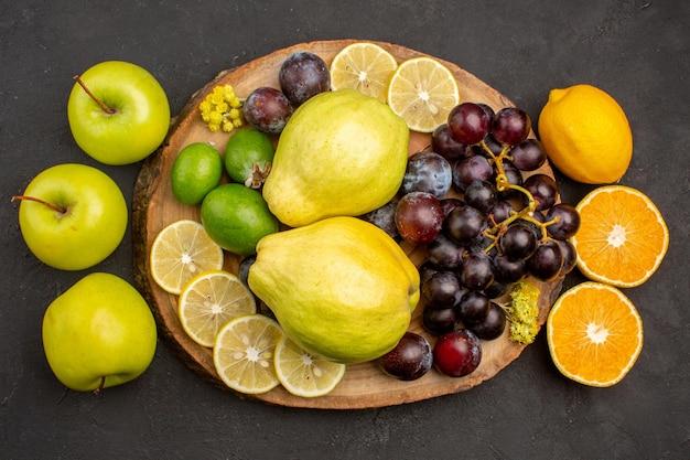 Draufsicht der frischen fruchtzusammensetzung ausgereifte und reife früchte auf einer dunklen oberfläche