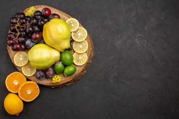Draufsicht der frischen fruchtzusammensetzung in scheiben geschnitten und reif auf dunkler oberfläche fruchtreife ausgereifte gesundheit frisch