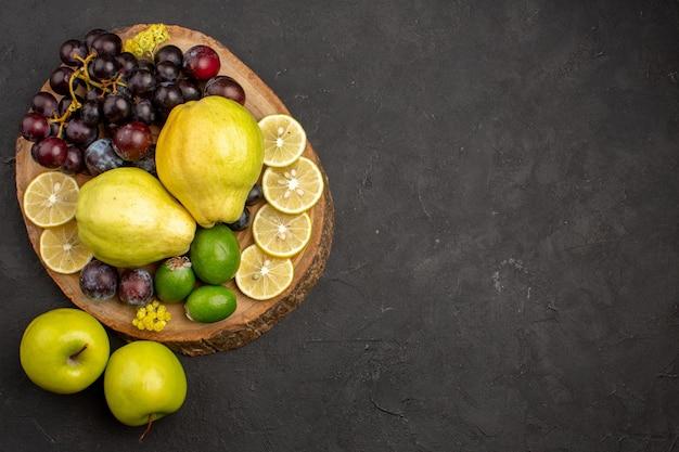 Draufsicht der frischen fruchtzusammensetzung in scheiben geschnitten und reif auf dunkler oberfläche früchte reife frische, ausgereifte gesundheit