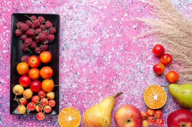 Draufsicht der frischen früchte himbeeren und pflaumen innerhalb der schwarzen form auf der rosa oberfläche