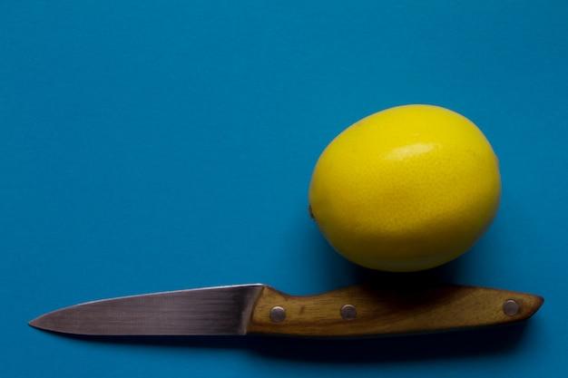 Draufsicht der frischen gelben zitrone und des messers