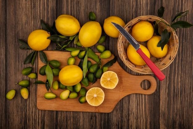 Draufsicht der frischen gelben zitronen auf einem eimer mit messer mit zitronen und kinkans auf einem hölzernen küchenbrett auf einem hölzernen hintergrund