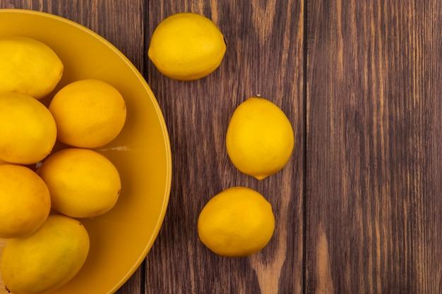 Draufsicht der frischen gelbhäutigen zitronen auf einem gelben teller auf einer holzwand mit kopierraum