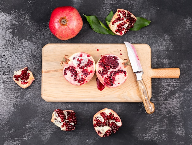 Draufsicht der frischen granatäpfel mit messer auf hölzernem schneidebrett auf dunkler oberfläche