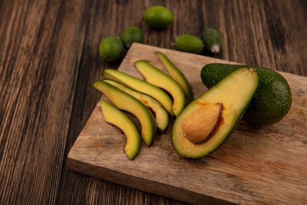 Draufsicht der frischen grünhäutigen avocados auf einem hölzernen küchenbrett mit feijoas lokalisiert auf einem hölzernen hintergrund