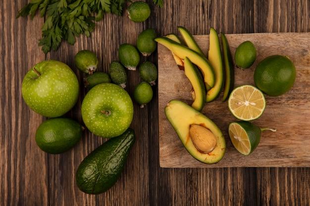 Draufsicht der frischen halben avocado mit scheiben auf einem hölzernen küchenbrett mit äpfeln feijoas kalk und petersilie lokalisiert auf einer hölzernen oberfläche