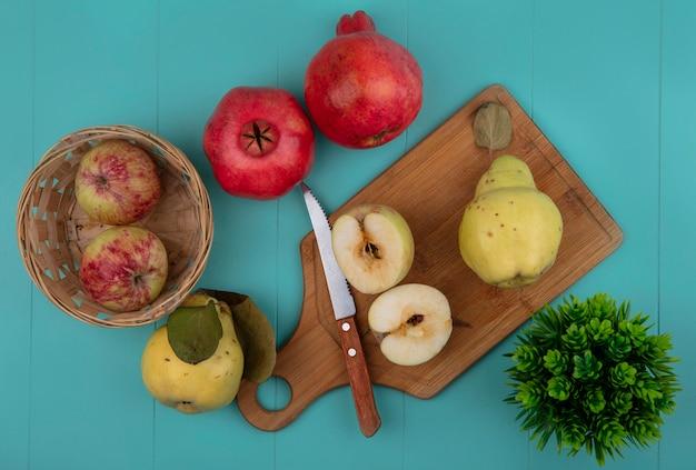 Draufsicht der frischen halbierten äpfel auf einem hölzernen küchenbrett mit messer mit ganzen äpfeln auf einem eimer mit quitten lokalisiert auf einem blauen hintergrund