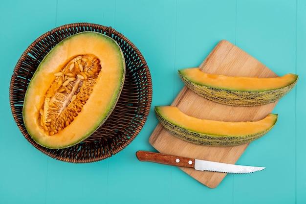 Draufsicht der frischen halbierten melone melone auf eimer mit melonenscheiben auf holz küchenbrett mit messer auf blau