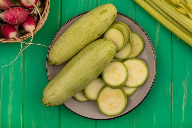 Draufsicht der frischen hellgrünen zucchini auf einem teller mit radieschen auf einem eimer mit sellerie lokalisiert auf einer grünen holzwand