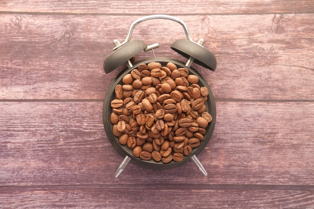 Draufsicht der frischen kaffeebohnen und des weckers auf holztisch