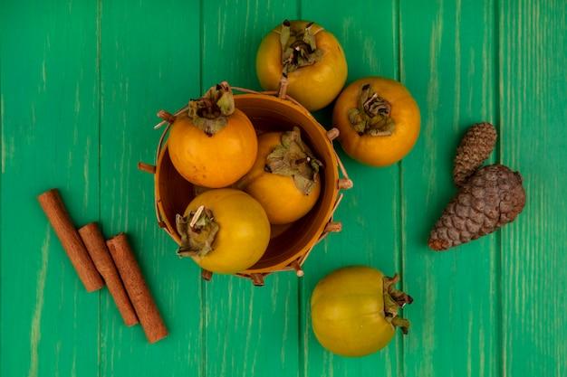 Draufsicht der frischen kakifruchtfrüchte auf einem eimer mit zimtstangen auf einem grünen holztisch