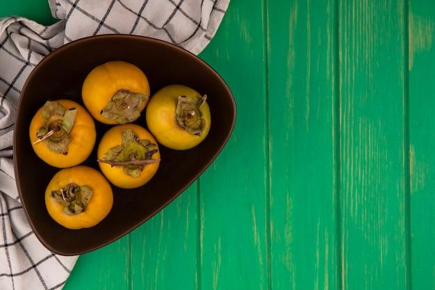 Draufsicht der frischen kakifruchtfrüchte auf einer schüssel auf einem karierten tuch auf einem grünen holztisch mit kopienraum