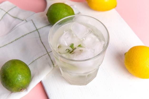Draufsicht der frischen kalten limonade mit eis im glas zusammen mit frischen zitronen auf der rosa oberfläche