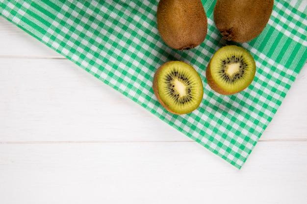 Draufsicht der frischen kiwifrucht auf karierter serviette auf weiß mit kopienraum