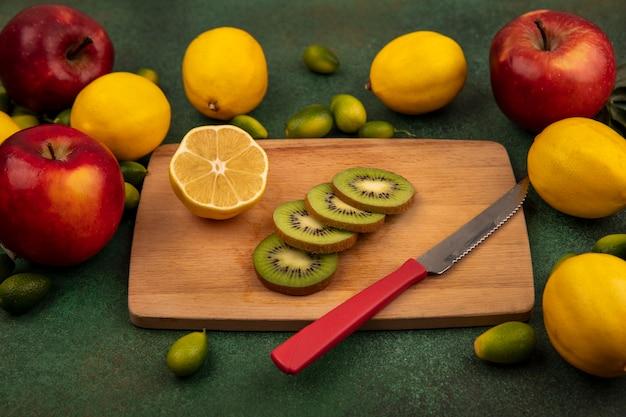Draufsicht der frischen kiwischeiben auf einem hölzernen küchenbrett mit messer mit zitronen und bunten äpfeln lokalisiert auf einer grünen oberfläche