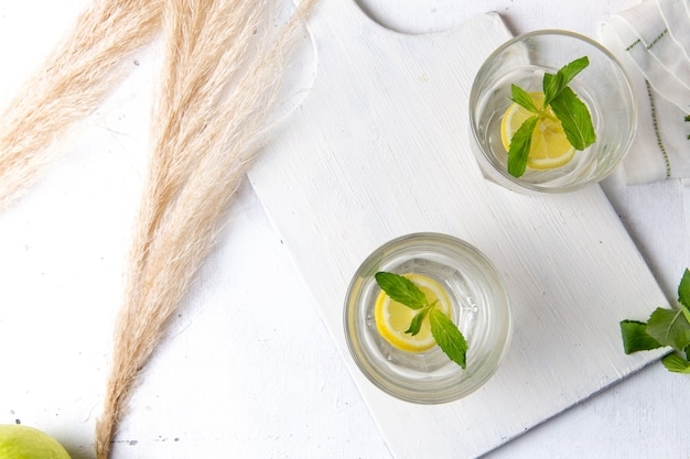 Draufsicht der frischen kühlen limonade mit geschnittenen zitronen innerhalb der gläser auf der weißen oberfläche