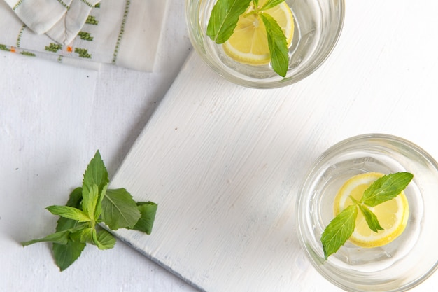 Draufsicht der frischen kühlen limonade mit geschnittenen zitronen innerhalb der gläser auf hellweißer oberfläche