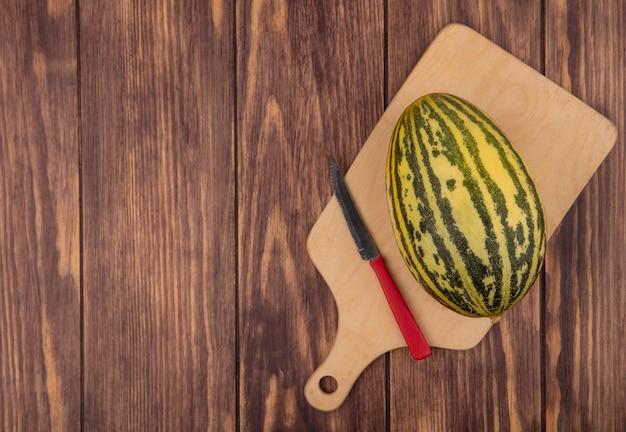 Draufsicht der frischen melone melone auf einem hölzernen küchenbrett mit messer auf einer holzwand mit kopierraum