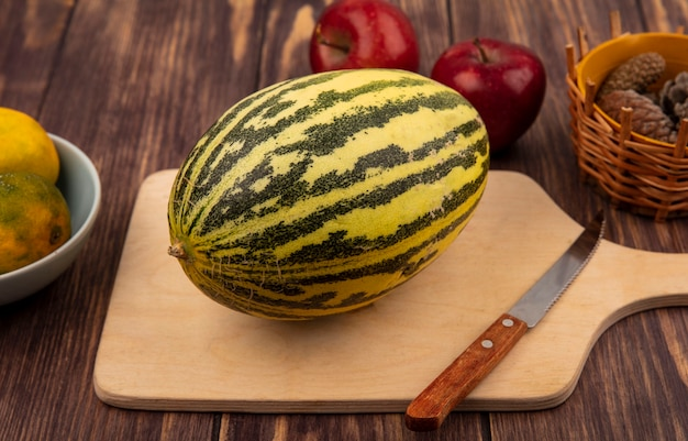 Draufsicht der frischen melone melone auf einem hölzernen küchenbrett mit messer mit äpfeln lokalisiert auf einer holzwand