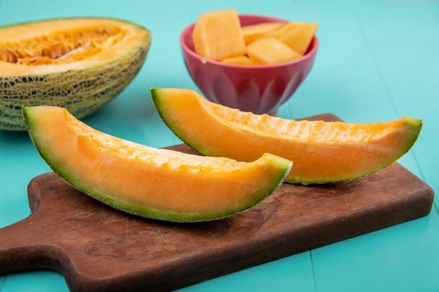 Draufsicht der frischen melonenscheiben der melone auf holzküchenbrett mit gehackten melonenscheiben auf schüssel auf blau