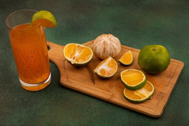 Draufsicht der frischen offenen und gehackten mandarinen auf einem hölzernen küchenbrett mit frischem fruchtsaft auf einem glas