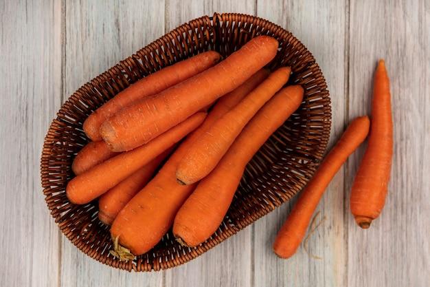 Draufsicht der frischen orange karotten auf einem eimer mit karotten lokalisiert auf einer grauen holzwand