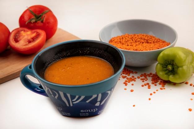 Draufsicht der frischen orange linsen auf einer schüssel mit orangenlinsensuppe auf einer schüssel mit tomaten auf einem hölzernen küchenbrett auf einer weißen wand